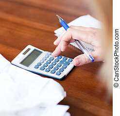 Close-up of a blond woman paying her bills