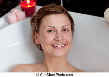 Smiling woman relaxing in a bath