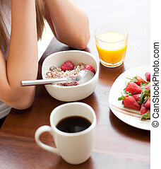 Close-up of a woman eating cereals with strawberries against...