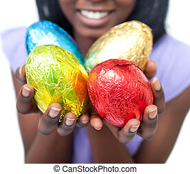 Close-up of a woman showing colorful Easter eggs against a...