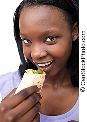 Smiling young woman eating a wrap