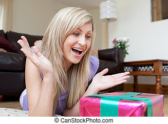 Surprised young woman opening gifts lying on the floor in...