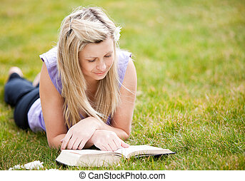 Beautiful woman reading a book in a park - Beautiful woman...