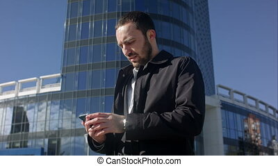 Man talking on the phone and looking on his watch outdoors