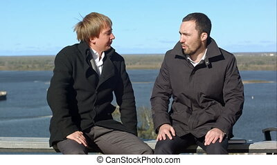 Two businesspersons sitting and talking