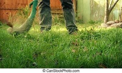 Man Using A Strimmer In The Garden - Low angle shot of...