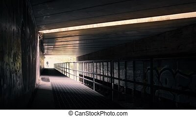 Man Walking Under Highway Bridge - Man on a walkway beneath...