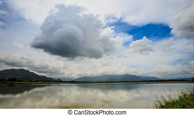 Motion of White Grey Clouds over Tranquil River Hills -...