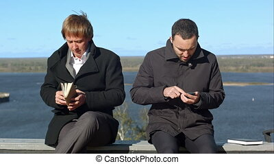 Two business people with phone and book. Professional shot...