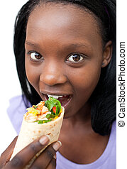 Young woman eating a wrap