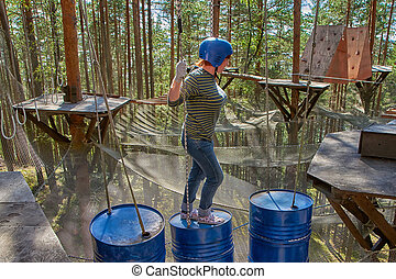 Woman passing the hanging puzzles in rope park
