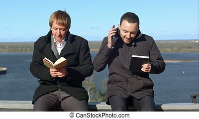 Young man on phone disturbs man withbook. Professional shot...