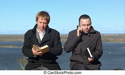 Young men talking on the phone and disturb businessman with booj