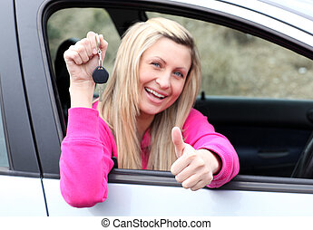 Happy female driver showing a key after bying a new car -...