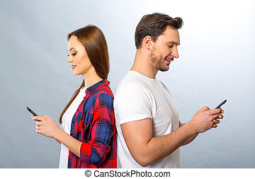 Young couple holding mobile phones - In pace with time...