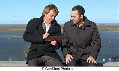 Having fun. Two man with tablet sitting on bench....