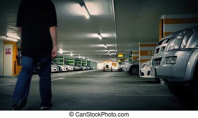 Man Walks To Car In Parking Garage - Young man walks over to...