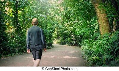 Man Walks Past On Path In Jungle - Man walking through dense...