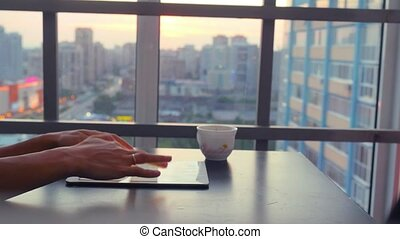 young business woman using tablet sitting in a restaurant with beautiful view from window on blurred city in lights and bokeh. 1920x1080