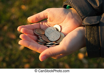 male hand with coins on background of grass