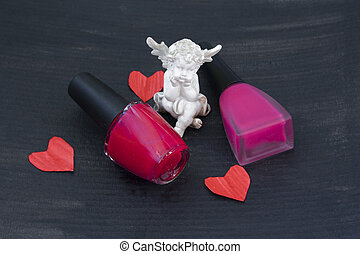 statuette of an angel, paper hearts and two bottles of varnish on the black background