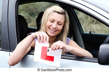 Happy young female driver tearing up her L sign sitting in...