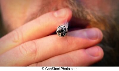 Smoking Cigarette Blows Smoke - Man smokes front on view in...