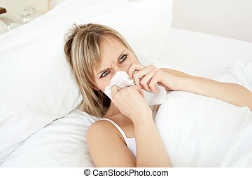 Sick young woman blowing lying on her bed