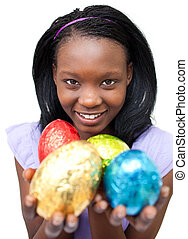 Smiling ethnic woman showing Easter eggs against a white...