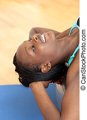 Smiling pretty woman doing sit-ups with a pilates ball