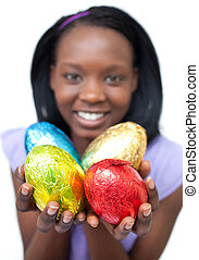 Happy ethnic woman showing Easter eggs against a white...