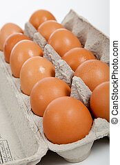 A dozen of brown eggs in a gray carton