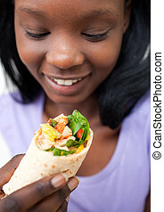 Afro-american young woman eating a wrap against a white...