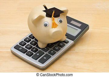 A golden piggy bank with grad cap and calculator on wood...