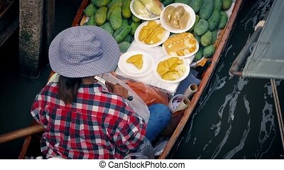 Woman Selling Food From River Boat - Woman cutting up...