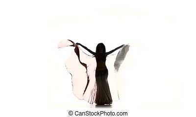 Beautiful slim exotic belly dancer with two wings starts dance, shaking her hips, on white, silhouette, shadow