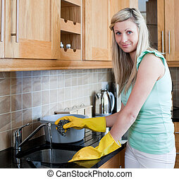 Smiling young woman cleaning in a kitchen at home