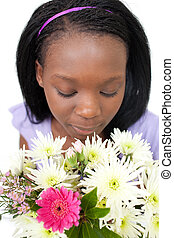 Charming young woman smelling flowers against a white...