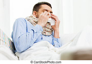 ill man blowing nose with paper napkin at home - healthcare,...