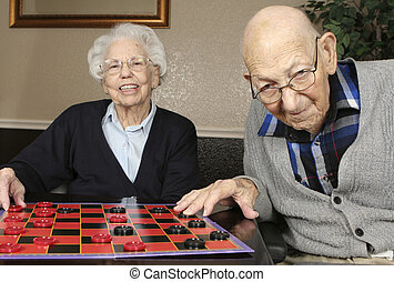 Active Seniors Playing Checkers - Active senior man and...
