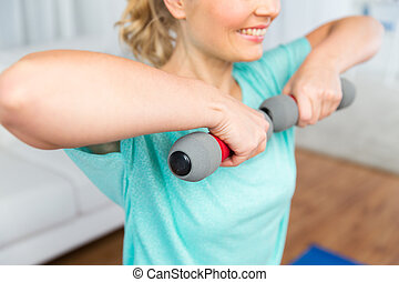 close up of woman exercising with dumbbell at home -...