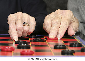 Checkers - Close up of senior adult hands and checkers