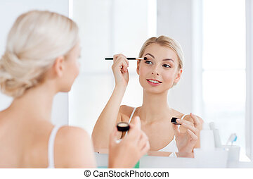 woman with makeup brush and eyeshade at bathroom - beauty,...