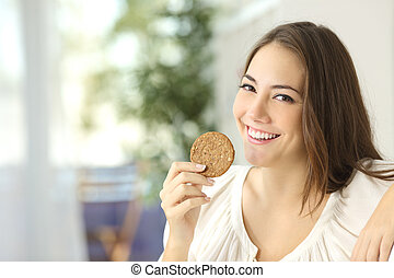Happy girl showing a dietetic cookie sitting on a couch at...