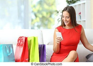 Woman in red buying with a smart phone - Woman in red using...