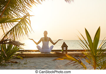 Young woman practicing yoga on the beach at sunset - Young...