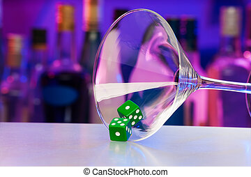 Green dice in cocktail glass with bar on back