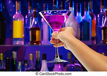 Cocktail glass in woman's hand with bar on back