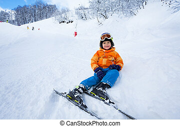 Little boy rest after ski lesson sitting in snow - Little...