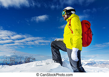 Skier man stand on top of the mountain